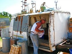 a man stands outside his rundown camper trailer